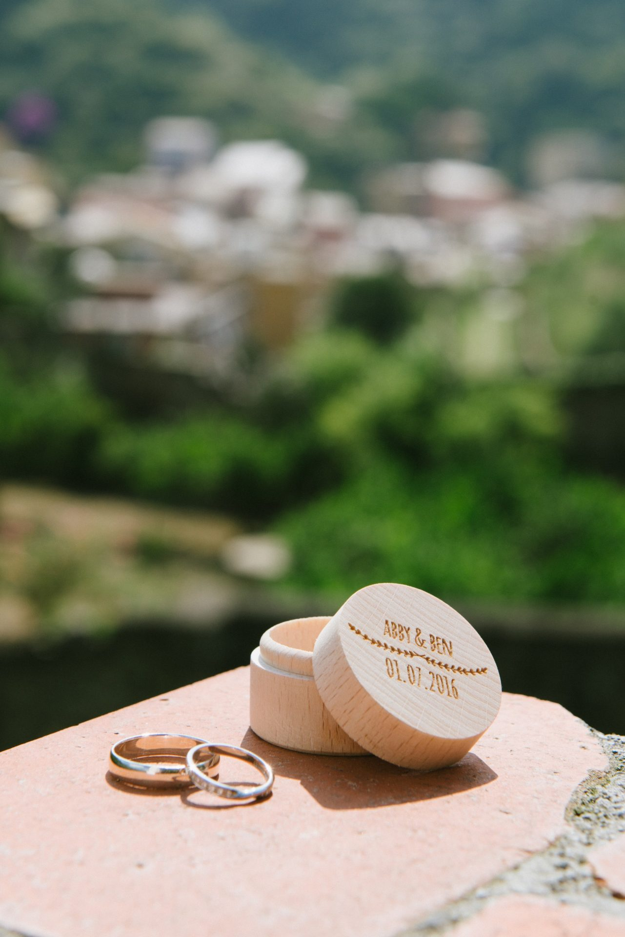 Wedding rings and box with Cinque Terre Italian landscape in the background