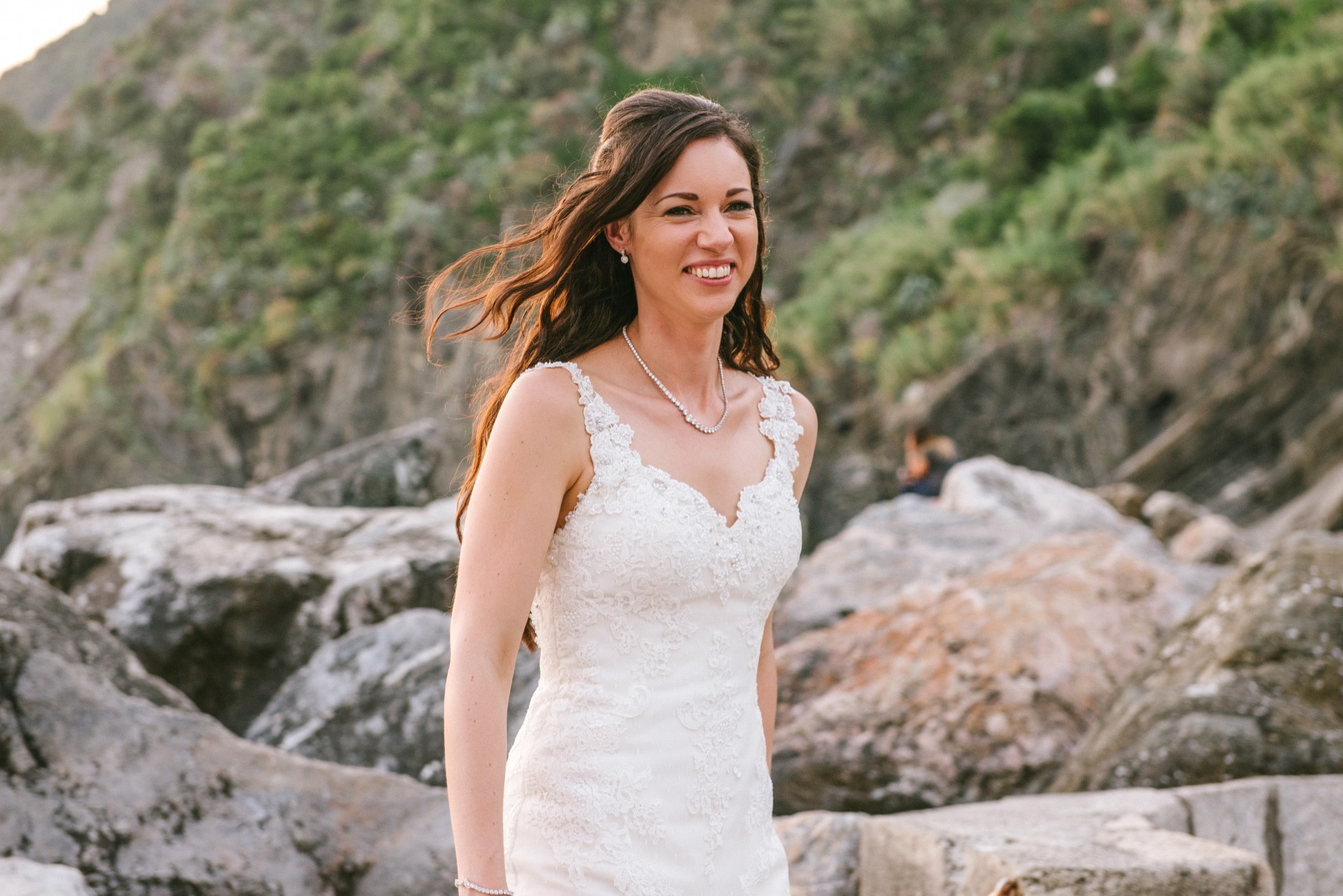 Bride smiling whilst walking in front of rocks during golden hour