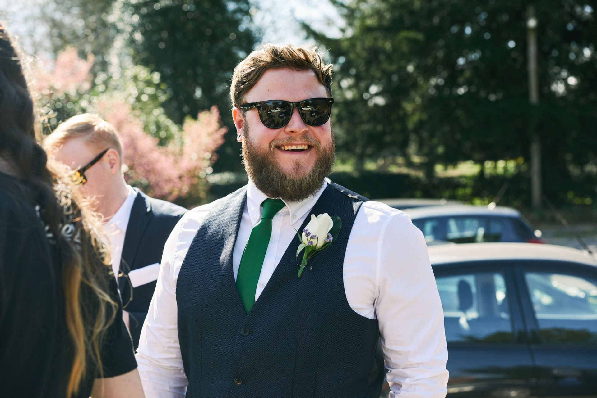 Natural wedding guest smiling whilst stood outside in a blue waistcoat