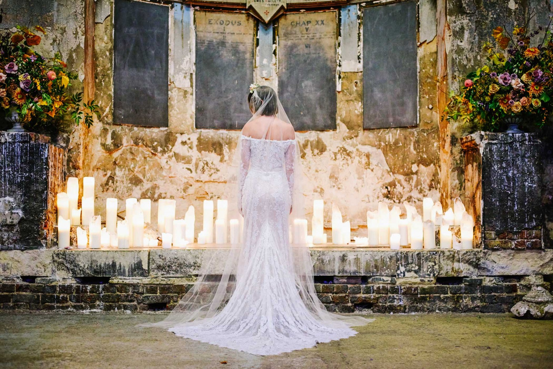 Bride posing in lace gown surrounded by candles in front of a decaying wall at the Asylum in London