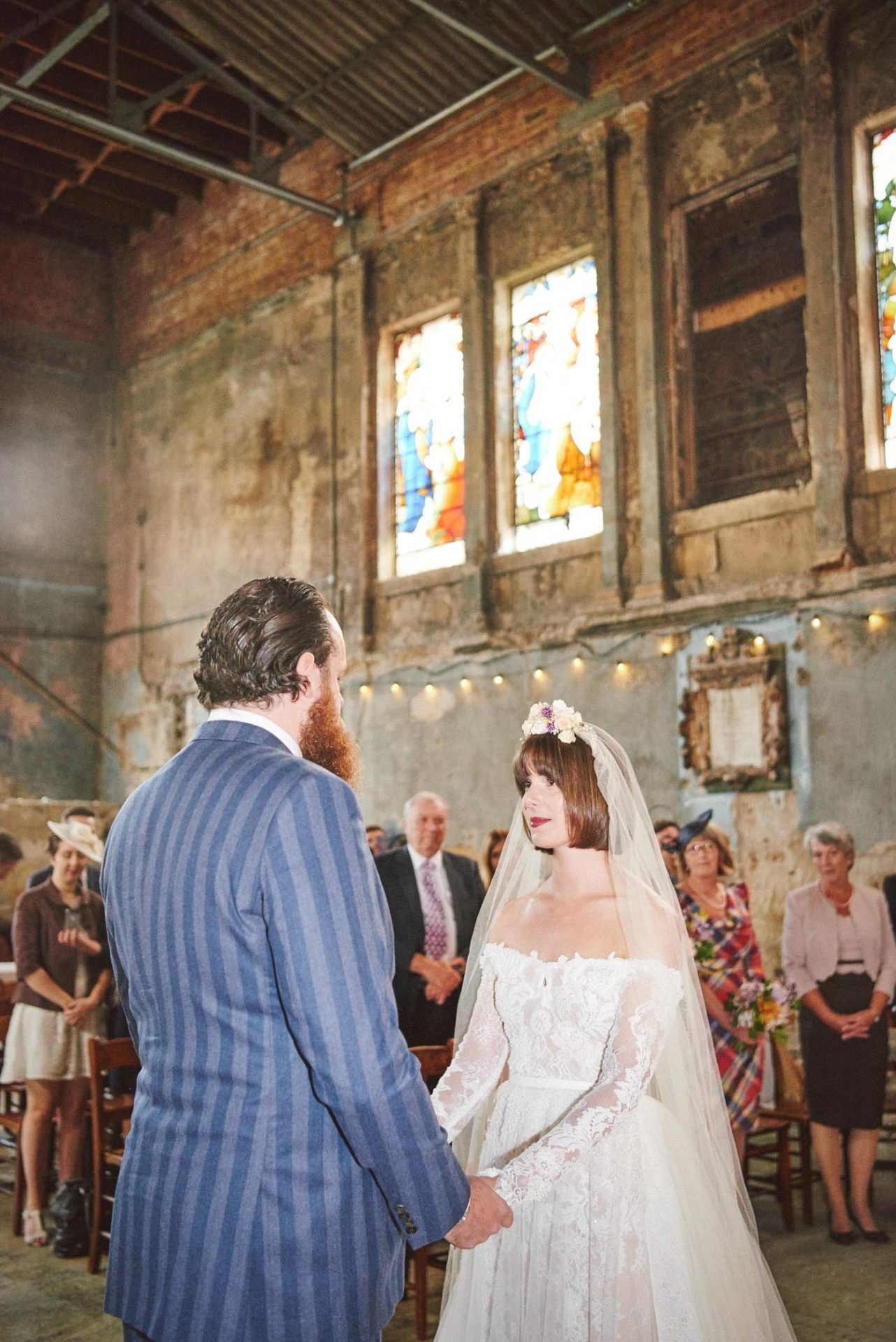 Bride and groom smiling whilst stood at the alter of the decaying asylum venue in London