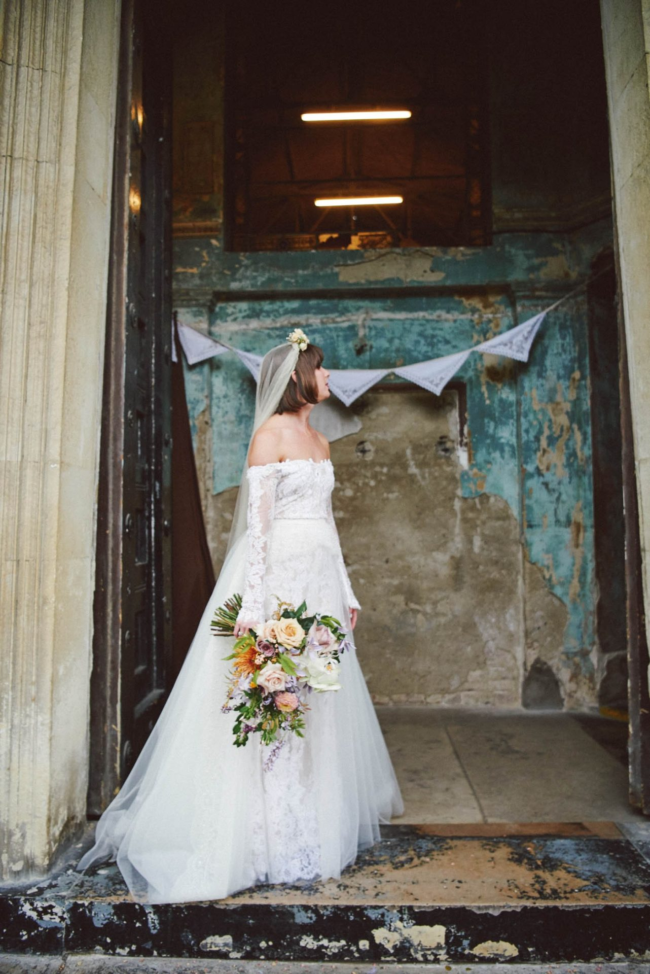 bride in vintage wedding dress stood in front of a decaying building called the Asylum