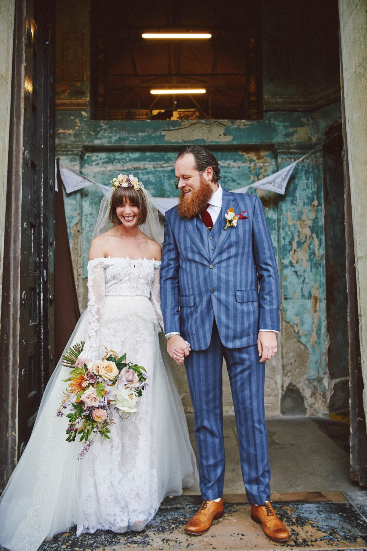 bride and groom laughing together in front of rustic entrance at the Asylum venue in London