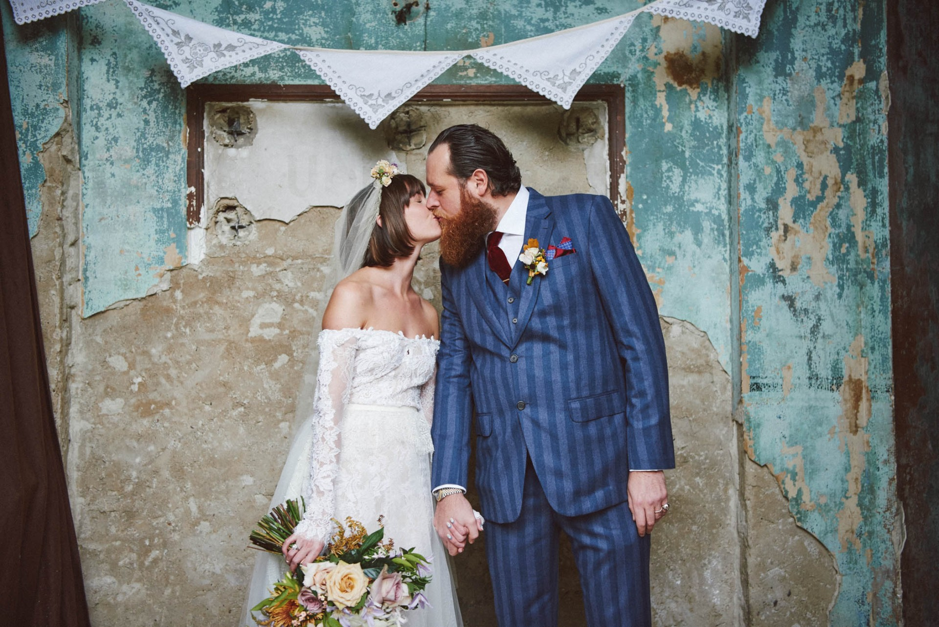 vintage looking bride and groom kissing in front a decaying wall at the Asylum in London