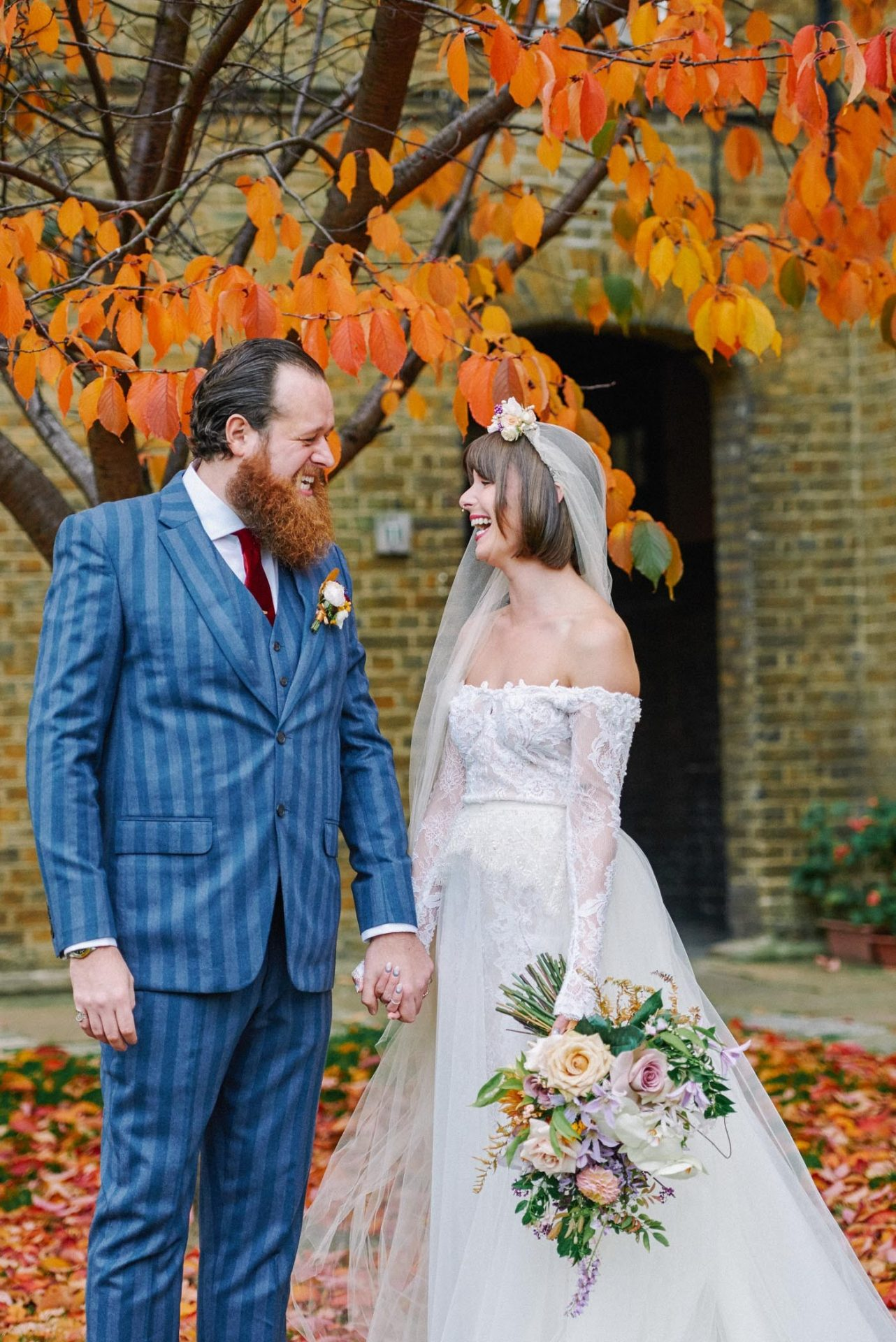vintage looking bride and groom holding hands whilst laughing surrounded by autumn leaves at the Asylum in London