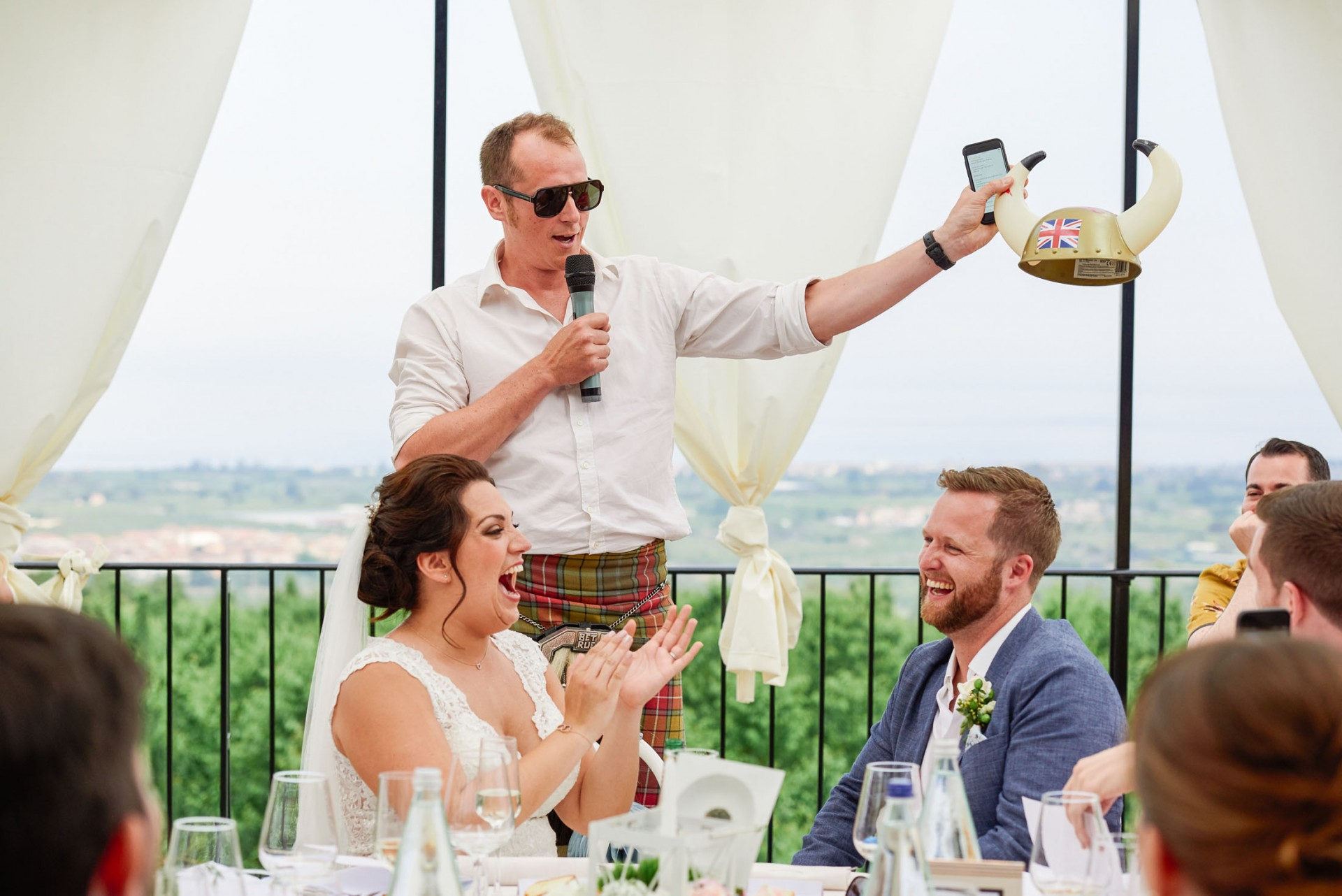 Best man giving a speech whilst bride and groom laugh on their wedding day. with a scenic view of Sicily behind them