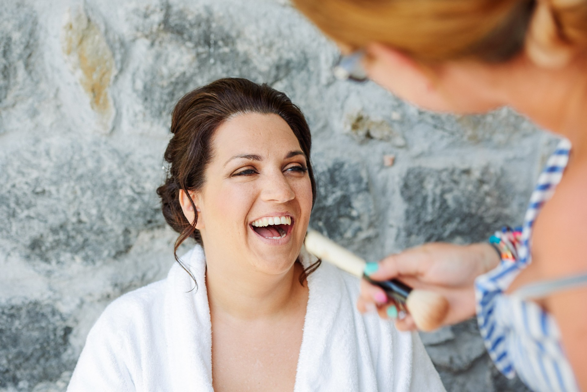 bride laughing whilst having her makeup applied in front of a grey stone wall