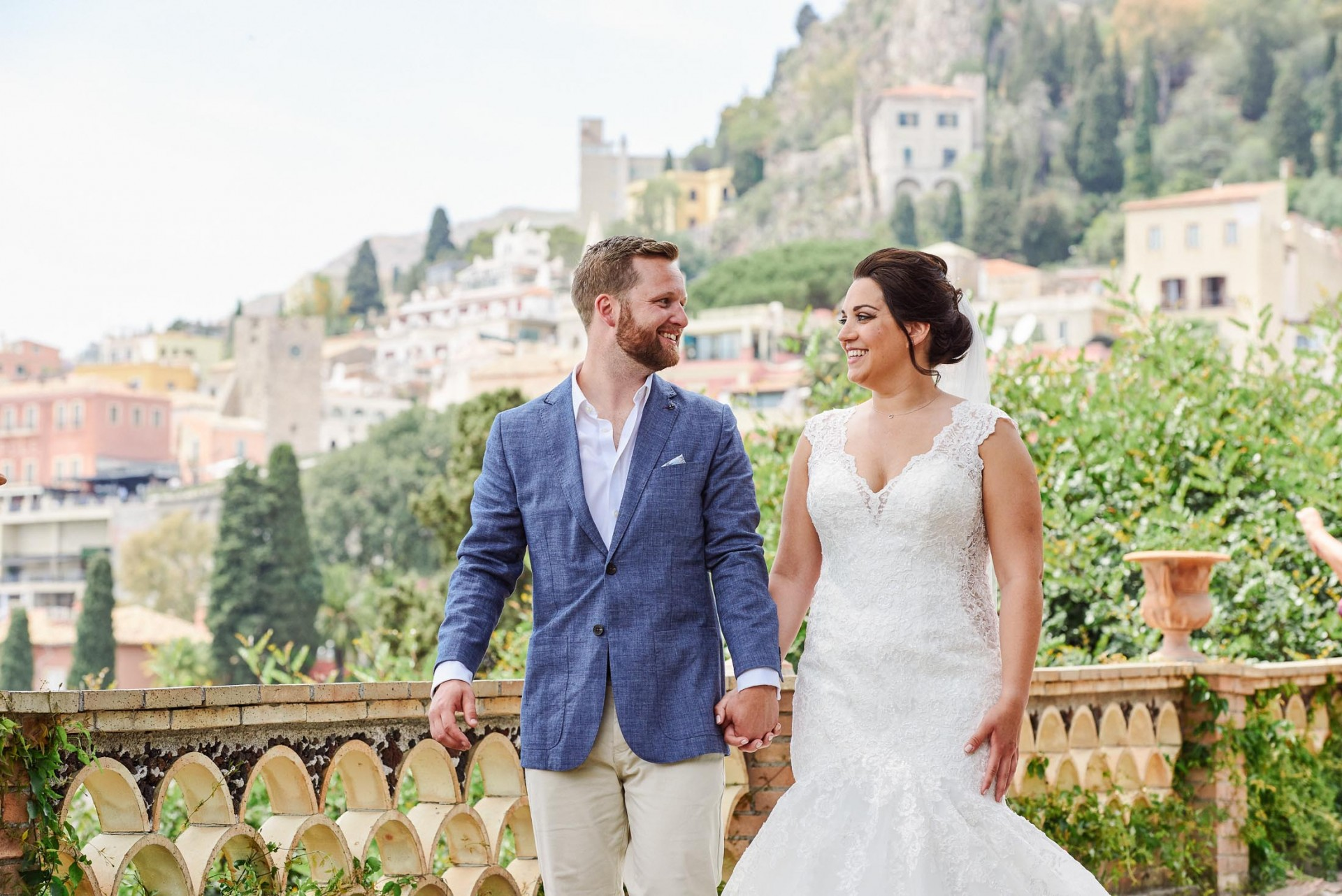 Bride and groom laughing together whilst walking with stunning views of Taormina, Sicily behind them