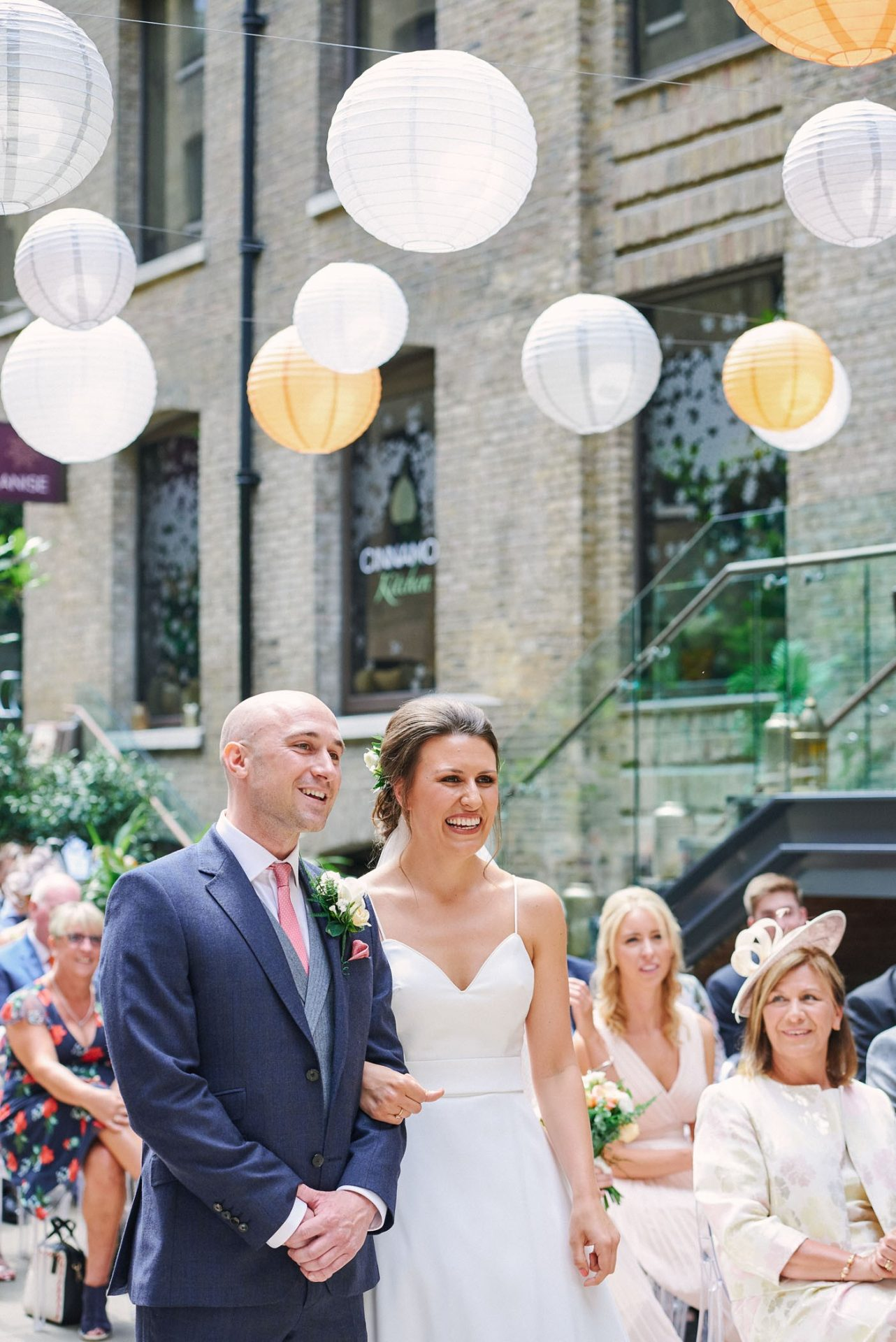 Bride and groom smiling during courtyard wedding ceremony at Devonshire Terrace in central London