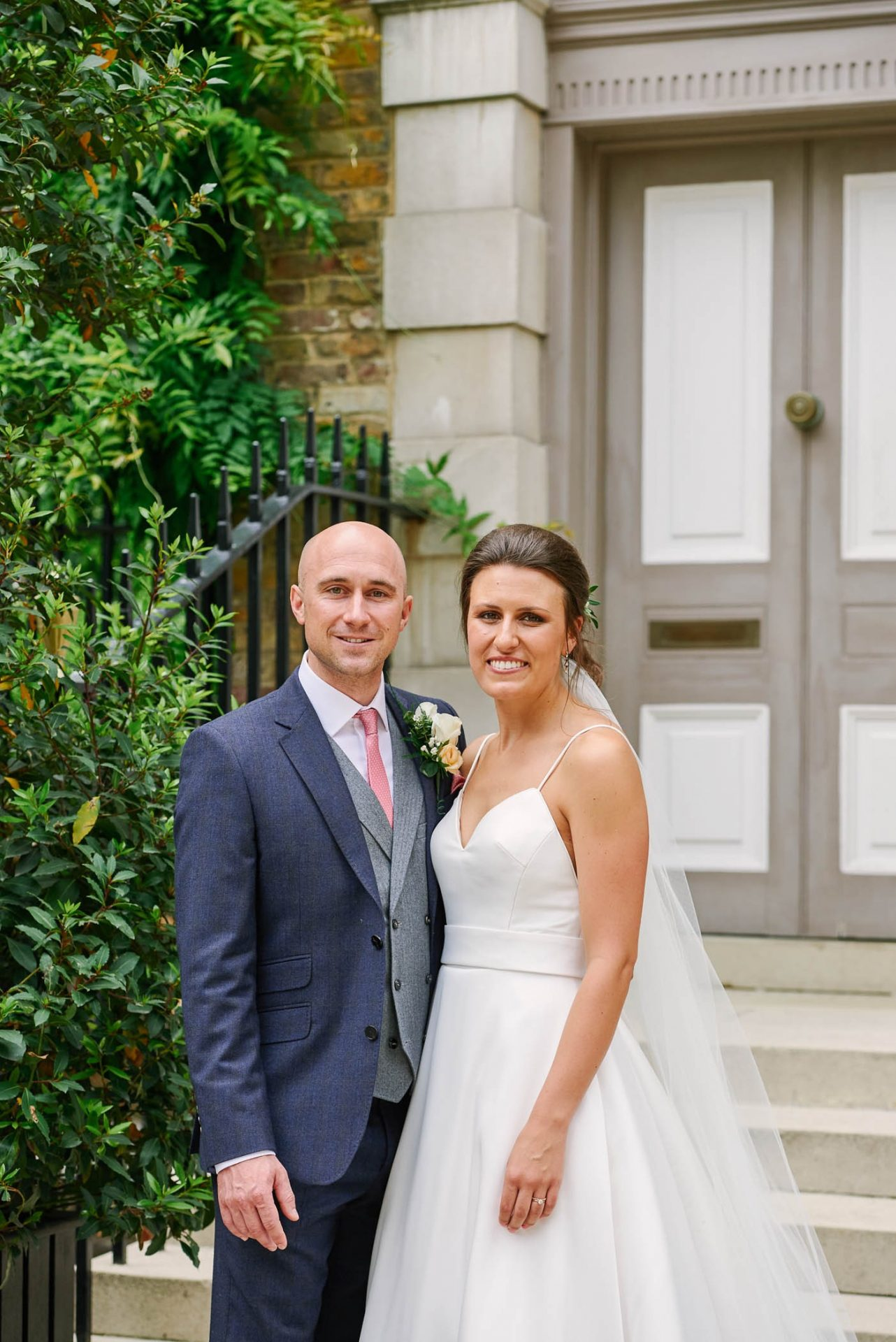 Bride and groom smiling in front of classic london doorway