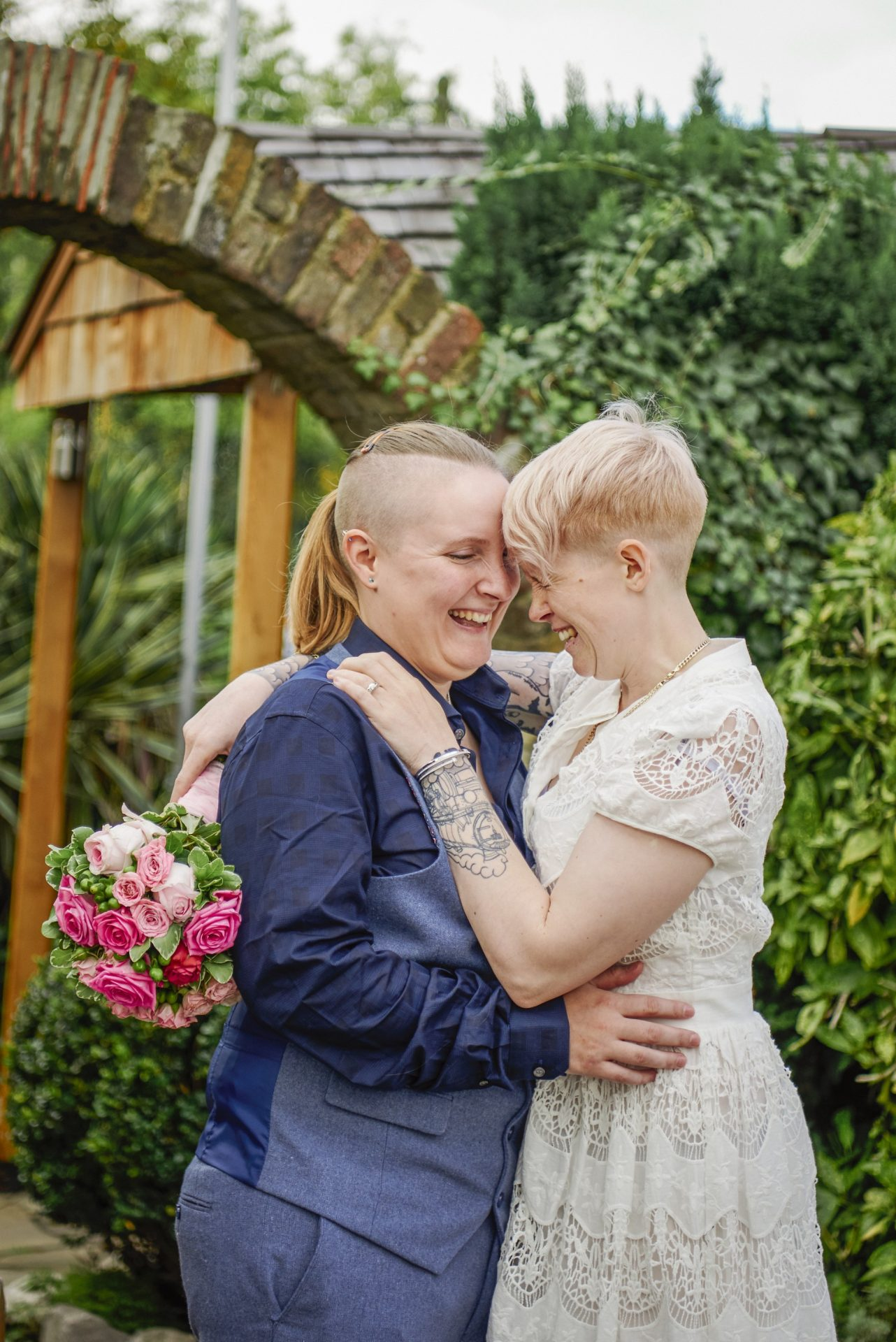 Lesbian brides laughing together on LGBT wedding day in front of green bushes