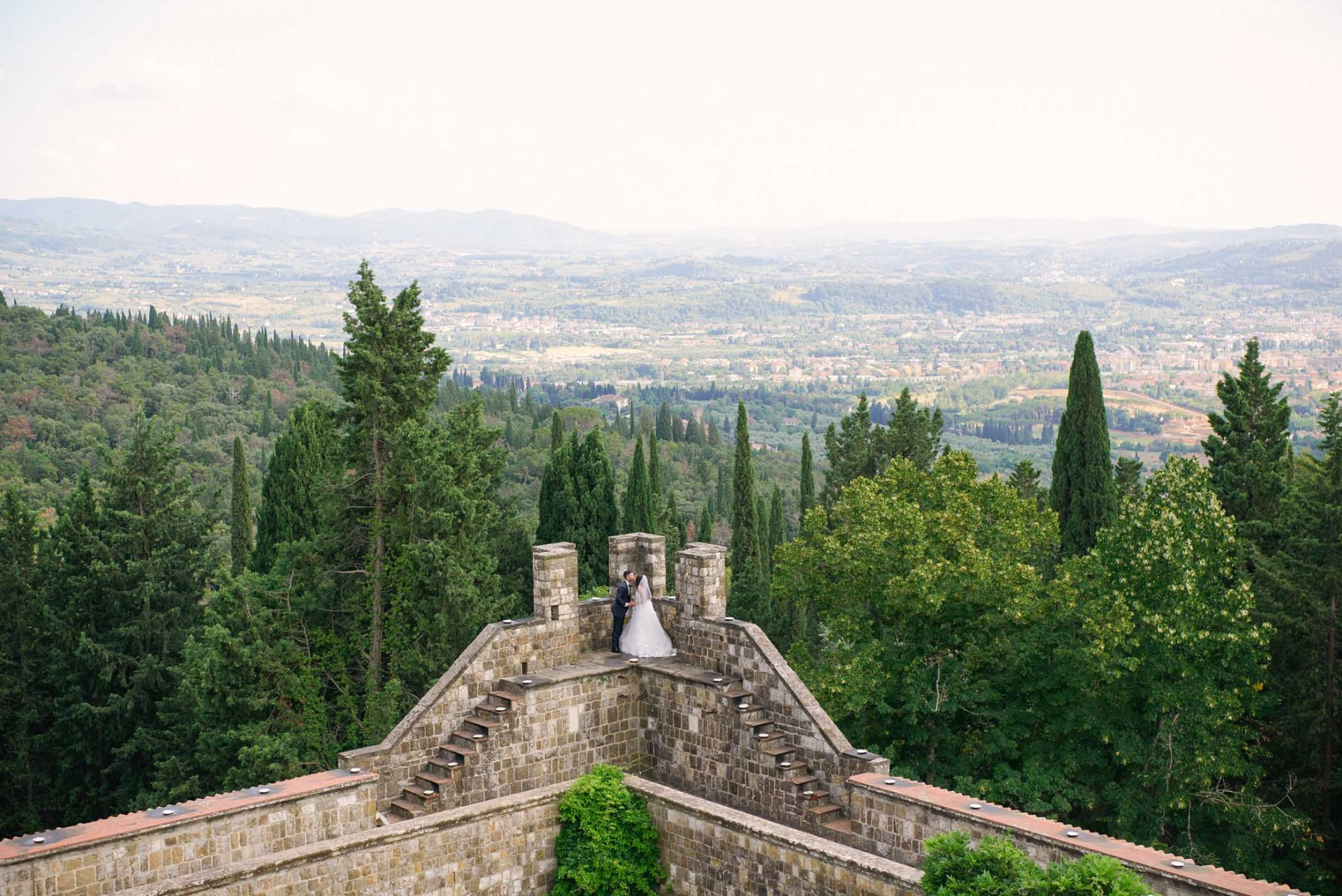 Bride and groom kissing on the edge of their Italian Castle venue overlooking views of Florence