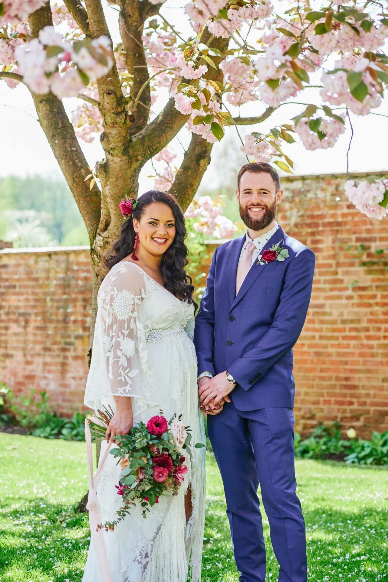 bohemian bride and groom stood under cherry blossom tree