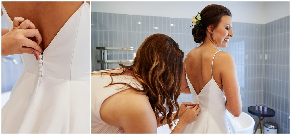 bride having her dress done up by her bridesmaid during bridal prep