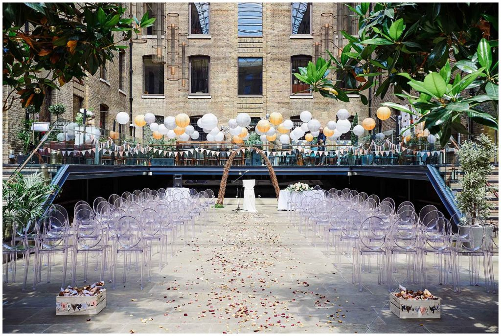 Empty wedding ceremony set up with colourful lanterns and clear chairs at Devonshire Terrace courtyard