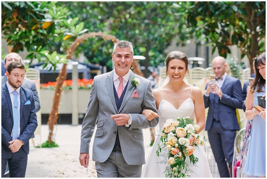 Bride and her dad walking down the aisle and smiling during her wedding ceremony at Devonshire Terrace Courtyard