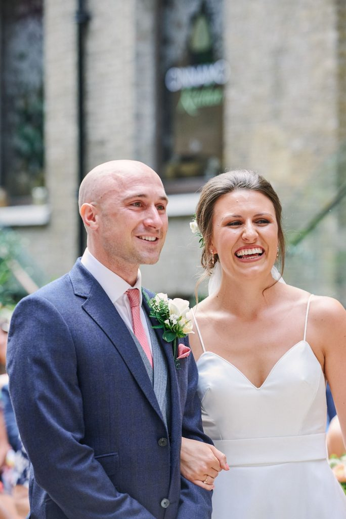 Bride and groom laughing together during wedding ceremony at Devonshire Terrace in central London