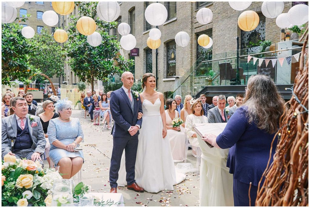 Bride and groom stood smiling together during their outdoor courtyard wedding ceremony