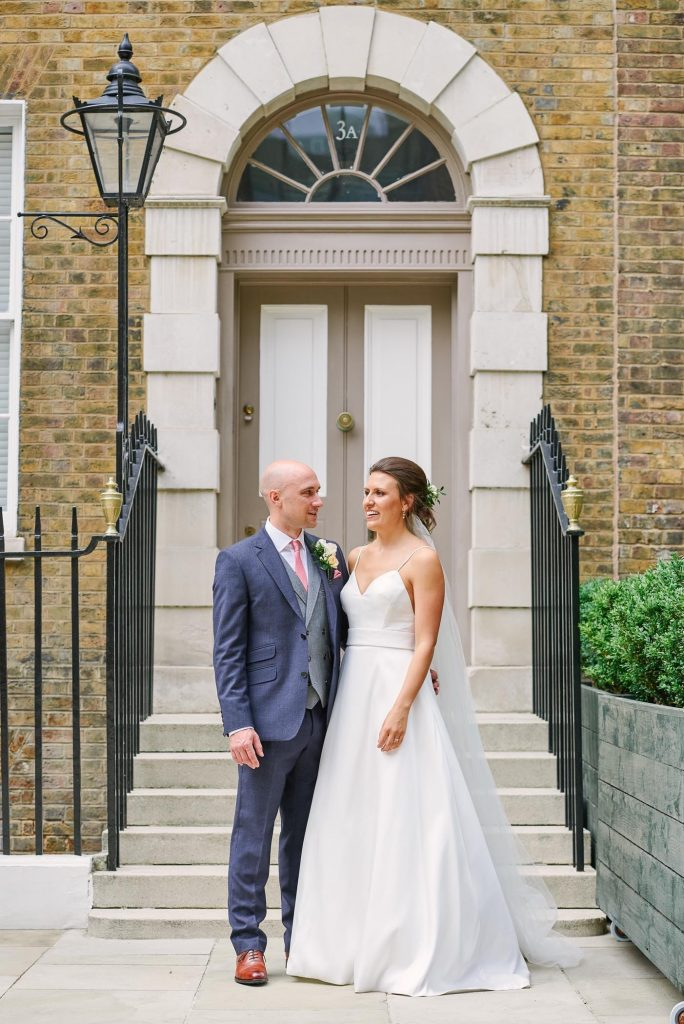 Bride and groom laughing together whilst stood in front of a classic London door at Devonshire Terrace.