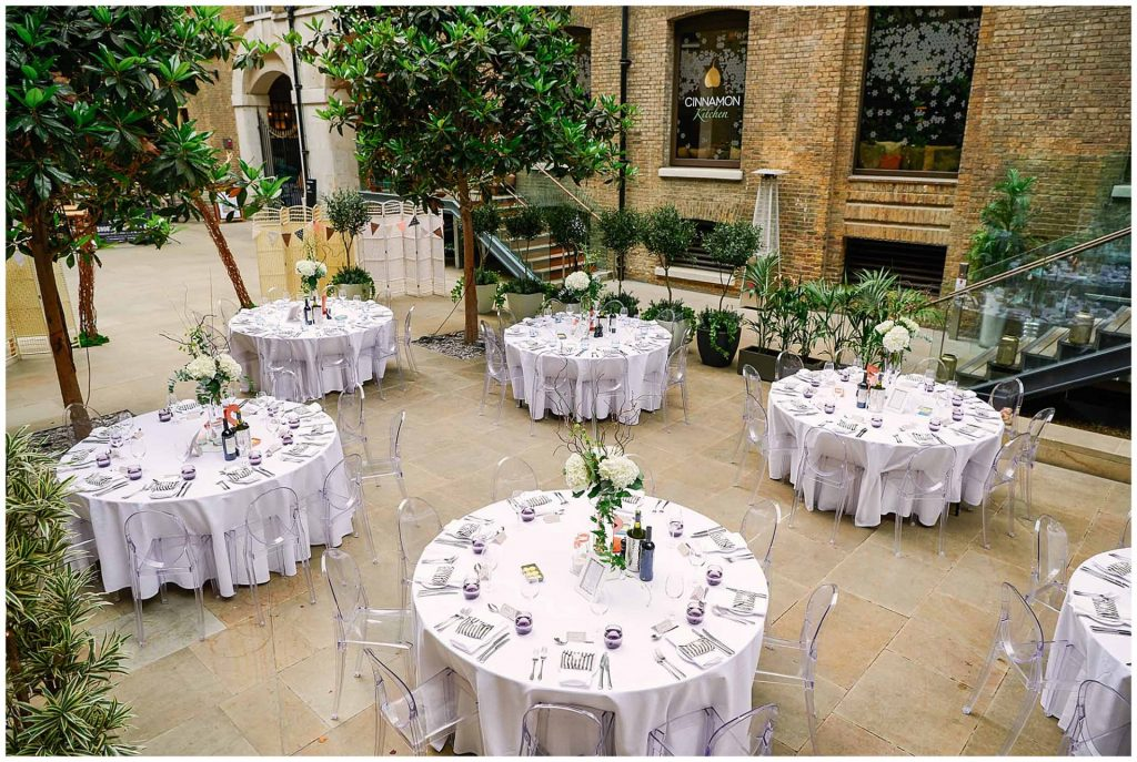 Empty round wedding table set up in the courtyard at Devonshire Terrance during wedding reception