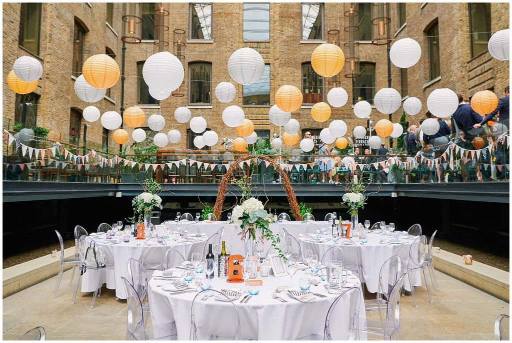 Empty wedding table set up in the courtyard at Devonshire Terrance in Central London. With orange and white lanterns hanging overhead.