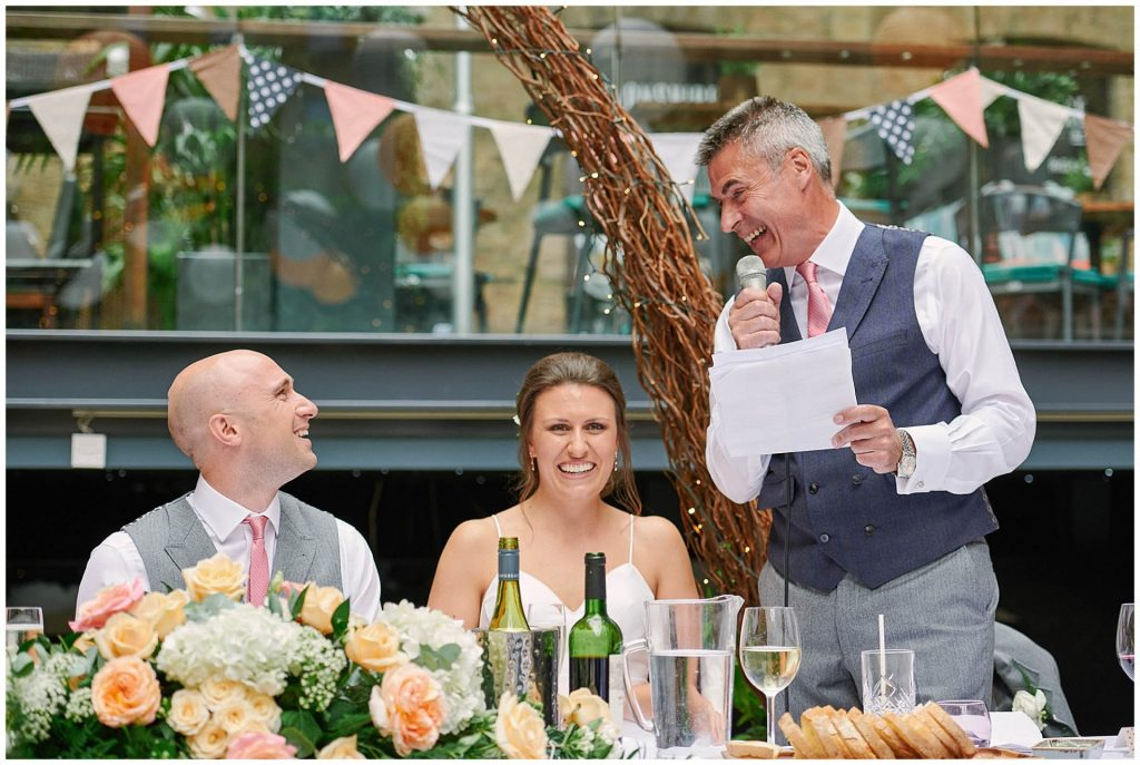 Father of the bride, bride and groom all laughing during the dads wedding speech at Devonshire Terrance in Central London.