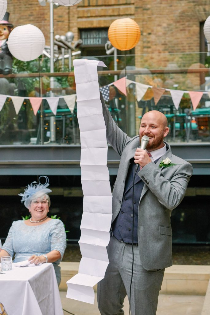 Best man laughing and holding up a long piece of paper during his wedding speech at Devonshire Terrance in Central London.
