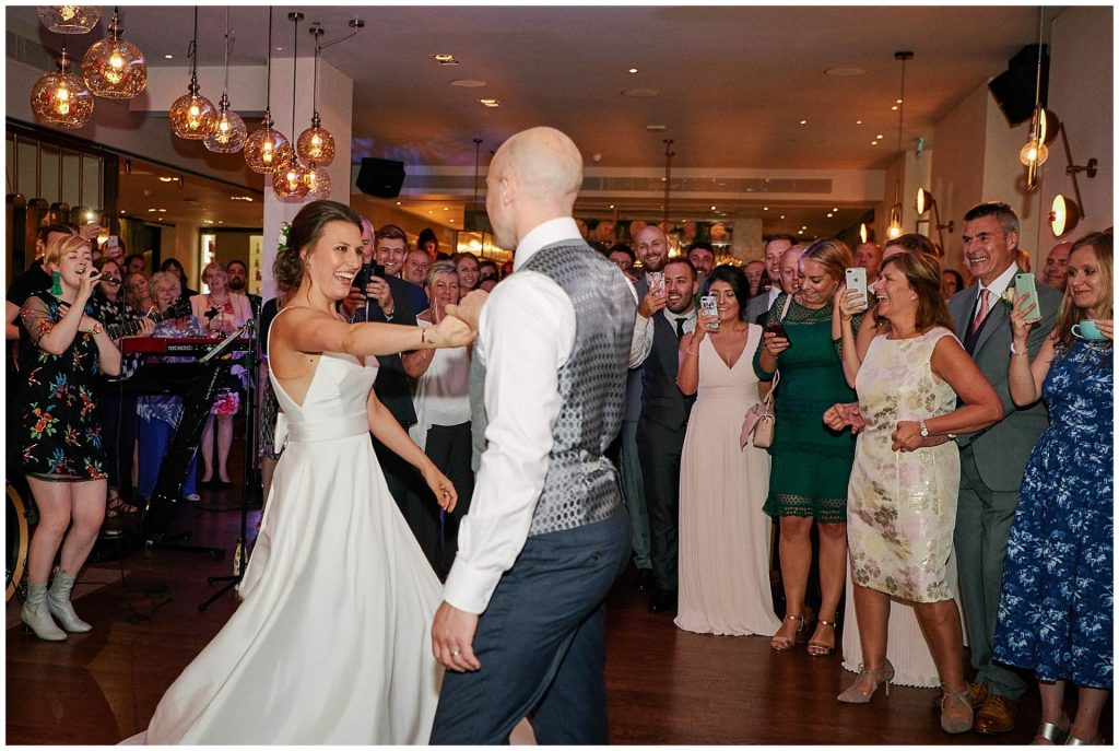 Bride and groom during first dance at Devonshire Terrance in Central London. Surrounded by wedding guests.