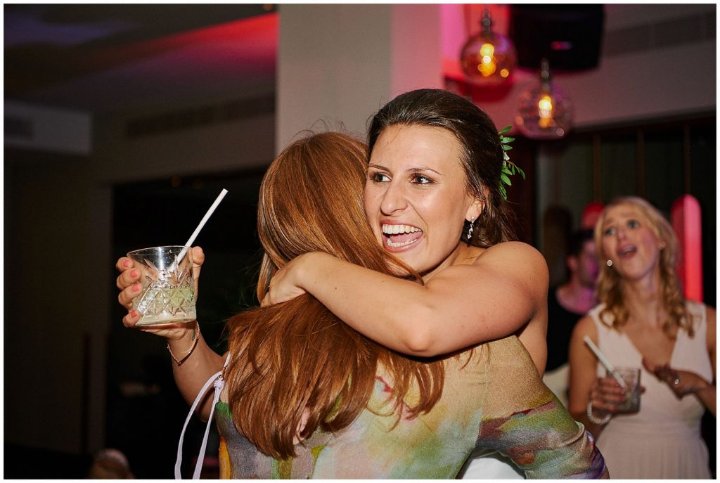 Bride smiling and hugging a guest whilst holding a drink on the dance  floor at Devonshire Terrance in Central London.