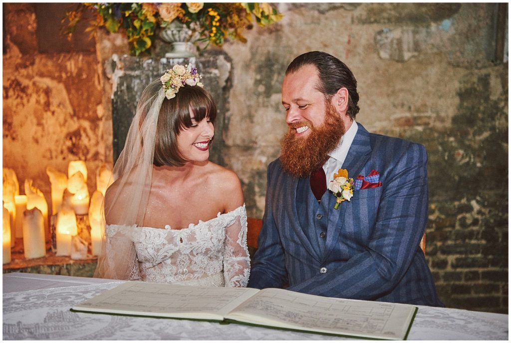Alternative vintage bride and groom signing the register at The Asylum in Peckham