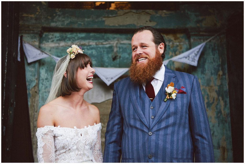 Bride and groom smiling together in front of a blue decaying wall at the Asylum in Peckham.