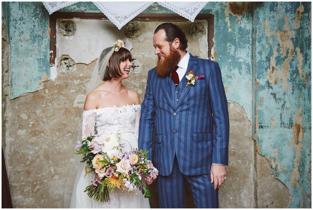Vintage bride and groom smiling in front of a decaying wall at the Asylum