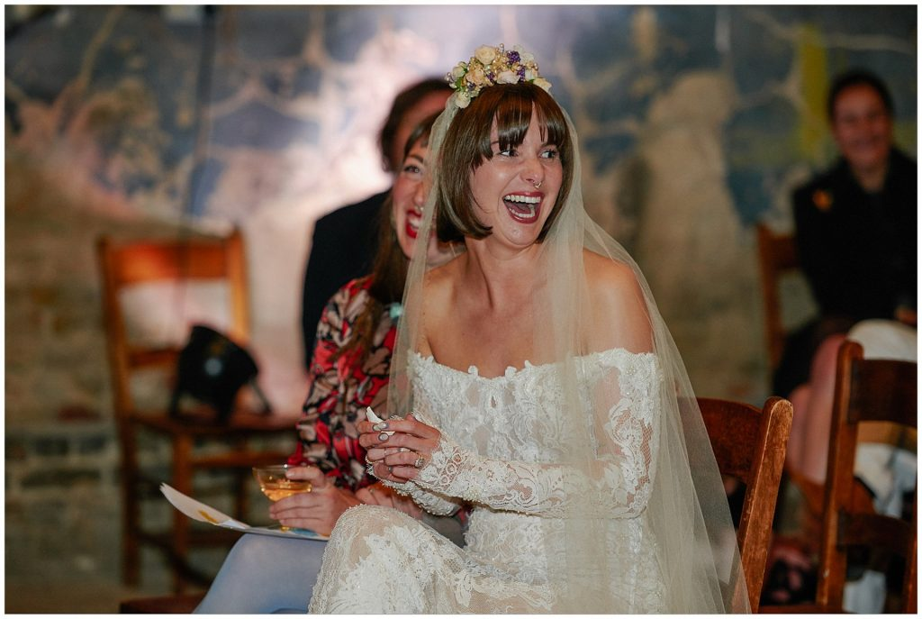 Bride laughing whilst sat in a decaying church venue in London