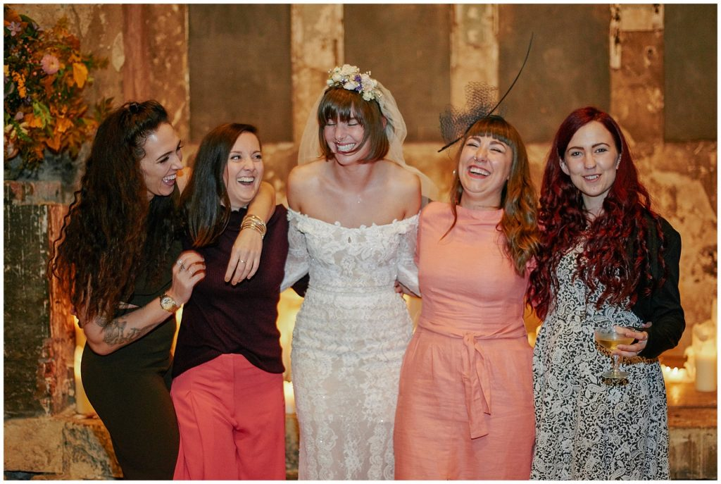 Bride laughing with her bridesmaids in a decaying candle lit asylum venue in London.