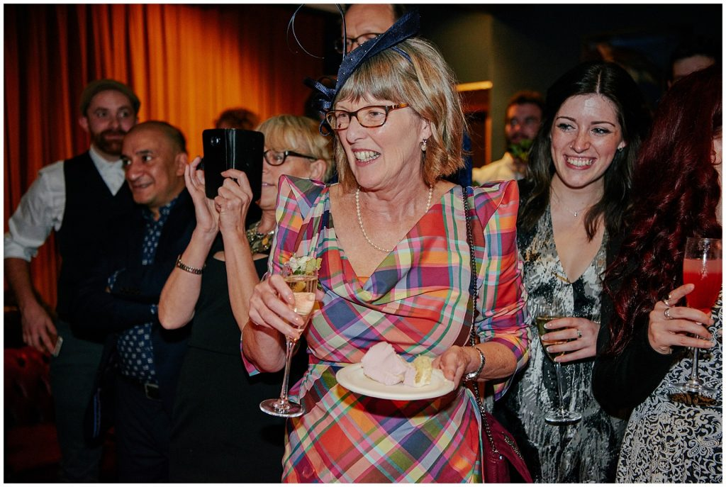 Mother of the bride laughing whilst holding cake and champagne at Shoreditch Townhouse.