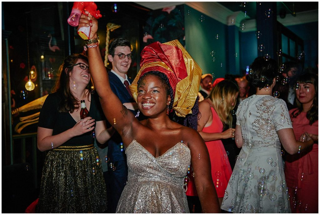 Caribbean wedding guest blowing bubbles in the air during reception party at Shoreditch Townhouse in London.