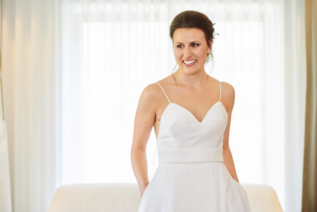 Bride in her wedding dress and smiling in hotel room in London