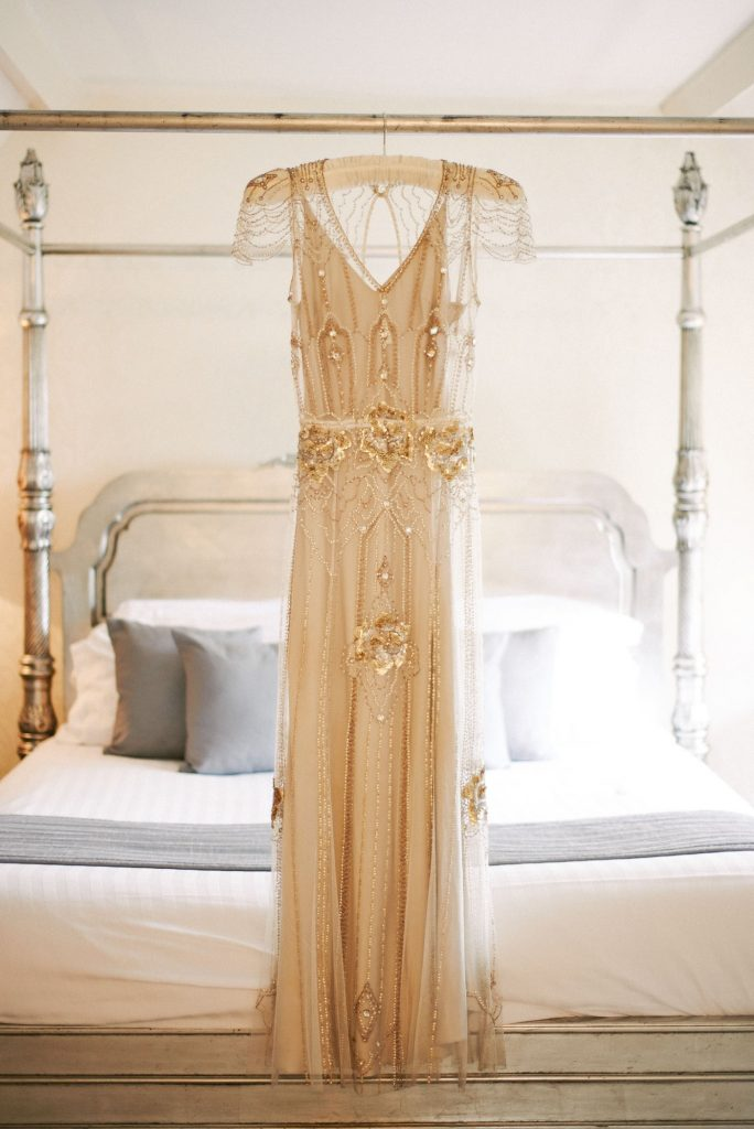 Jenny Peckham vintage wedding dress with gold sequins hung on white 4 poster bed in bridal suite at Woodhall Manor
