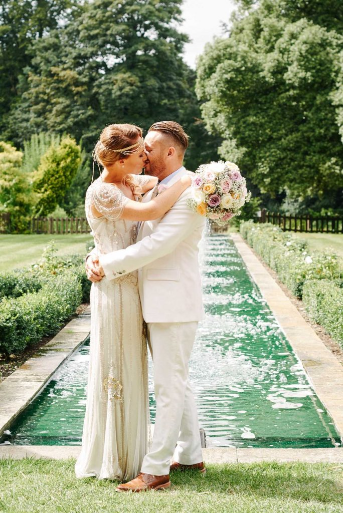 Bride and Groom kissing in front of a water feature whilst holding flowers on a sunny day at Woodhall Manor