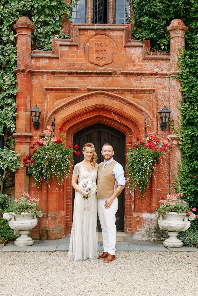 1920's style Bride and Groom in front of the red brick entrance at Woodhall Manor
