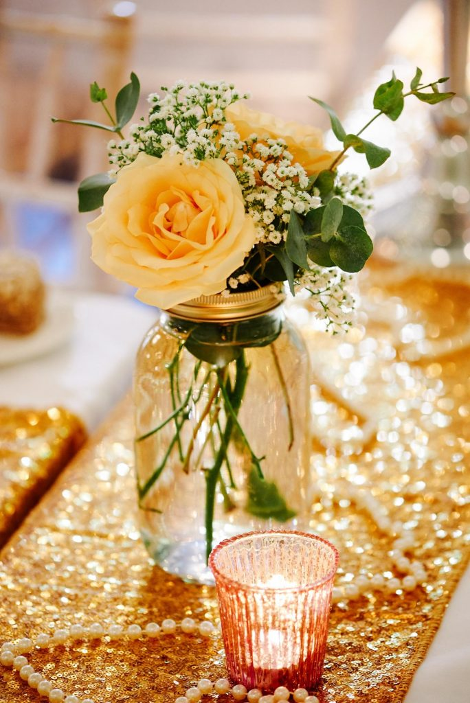 yellow rose in a jar on wedding table with gold sequined table runners.