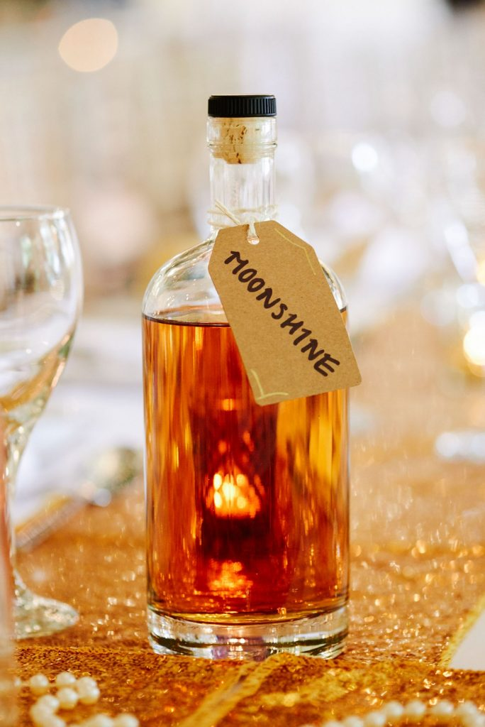 Bottle of moonshine on gold sequined wedding table at Great Gatsby themed wedding