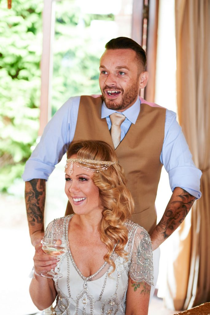 1920's style bride and groom laughing during speeches at Great Gatsby themed wedding