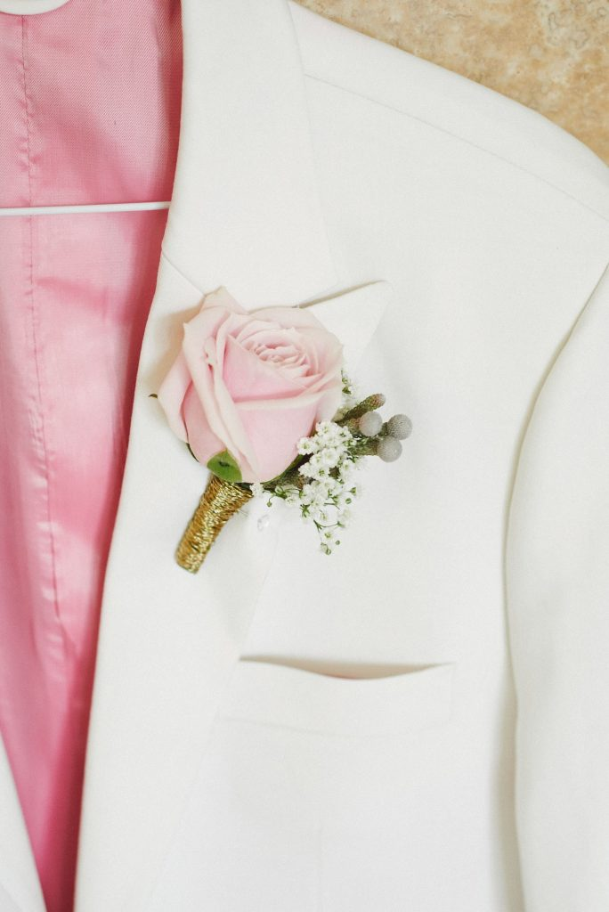 White groom suit with pink rose corsage pinned to the pocket