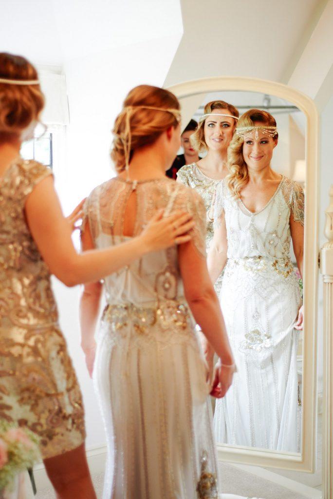 Bride smiling in mirror wearing vintage 1920's Jenny Peckham wedding dress