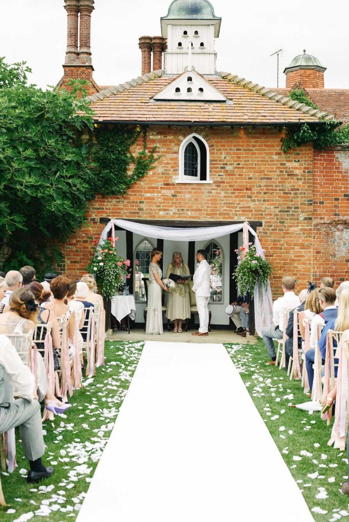 Bride & Groom stood at the end of the outdoor alter whilst friends and family watch them get married