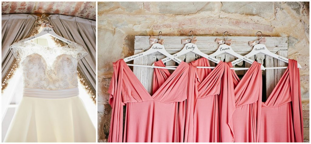 Pink bridesmaid dresses and white wedding dress hung up against rustic brick wall