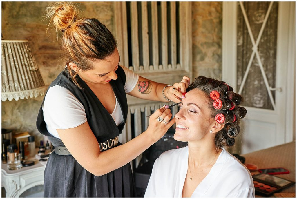 Bride having her makeup applied with her hair in rollers at the Villa le Fontanelle wedding venue in Florence, Italy