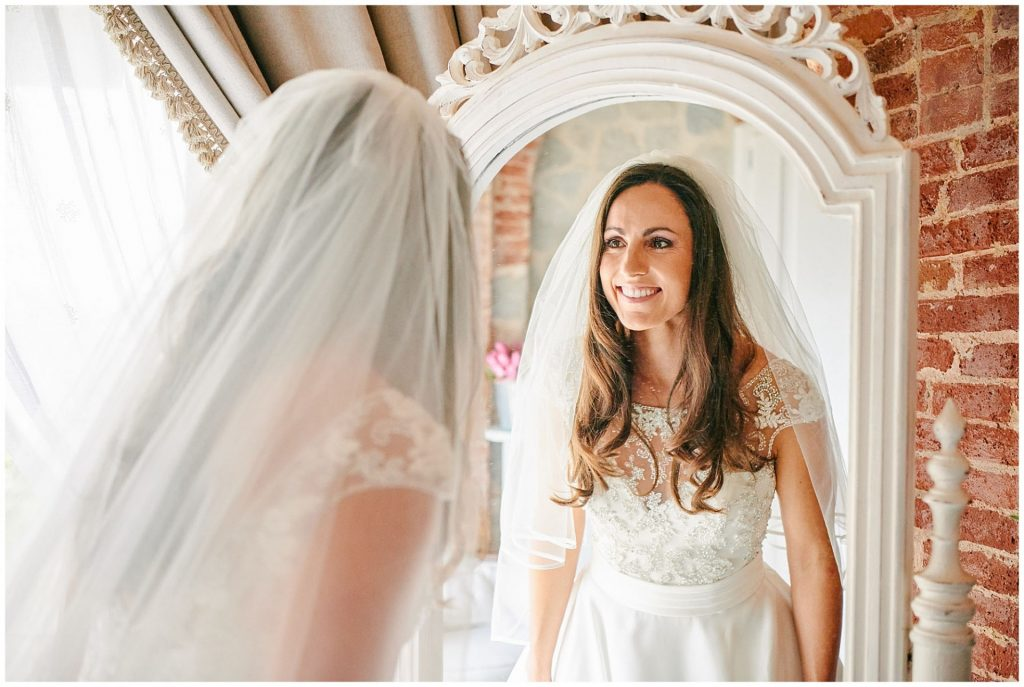 Bride smiling and looking in mirror at Villa le Fontanelle in Florence, Italy