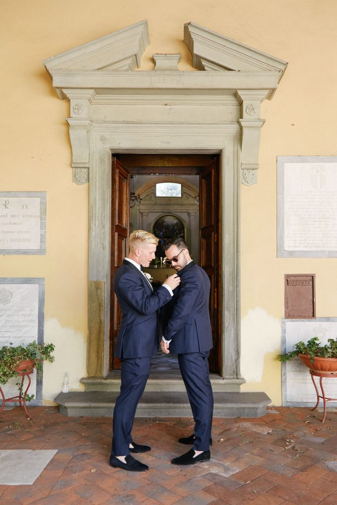 Groom and groomsmen adjusting their suits outside of the Catholic Church of Careggi in Florence, Italy